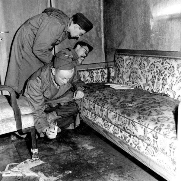 Soldados soviéticos examinan el sofá en el que presuntamente se suicidaron Hitler y Eva Braun.