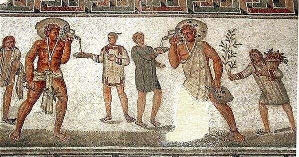 Los dos esclavos que llevan jarras de vino usan ropa típica de esclavos y un amuleto en contra del mal de ojo en un collar